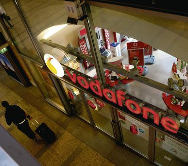 A man pulling a suitcase passes a Vodafone store