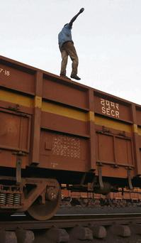 A worker walks along the wagon of a goods train at a railway yard in the western Indian city of Ahmedabad