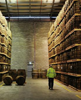 An employee passes barrels containing Jameson whiskey, produced by Irish Distillers Ltd., at the Pernod-Ricard distillery in Middleton.