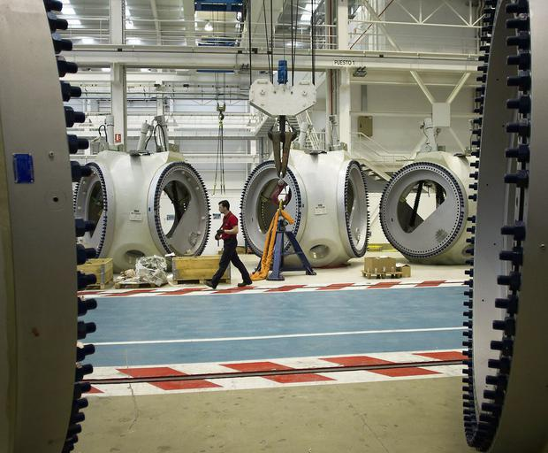 An employee passes wind turbine hub units during assembly at Acciona SA's Barasoain production plant in Navarra, Spain.
