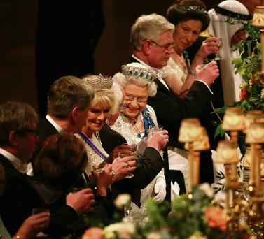 Queen Elizabeth speaks with President Michael D Higgins during the state banquet.