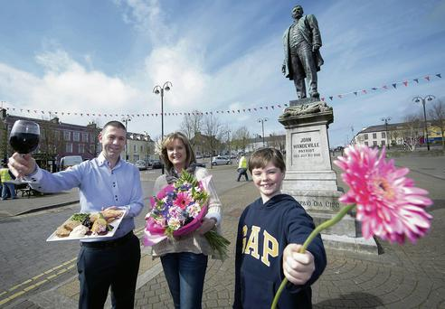 Mitchelstown business owners John O'Connor, left, of the Market Place Restaurant, and Una Fitzgerald of Flowers by Una, with her son Jake. Provision/Michael MacSweeney