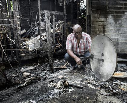 Happy Agamah, from Rathfarnham, examines the aftermath of the arson attempt on his apartment. Photo: David Conachy
