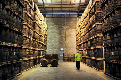 An employee passes American oak barrels containing Jameson whiskey, produced by Irish Distillers Ltd., at the Pernod-Ricard SA distillery in Midleton, Co Cork