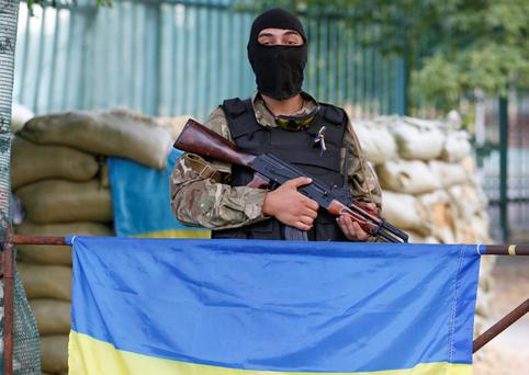"A soldier of Ukrainian self-defence battalion ""Azov"" stands guard at their base in the southern coastal town of Mariupol"