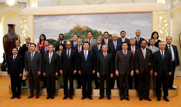 China's President Xi Jinping (centre) poses for a photo with guests at the Asian Infrastructure Investment Bank launch at the Great Hall of the People in Beijing last October