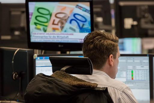 A financial trader monitors data on computer screens as a desktop television shows euro currency banknotes at the Frankfurt Stock Exchange in Frankfurt, Germany, on Monday, March 9, 2015. With the European Central Bank buying its first government bonds this week to shore up the region's economy, options traders are showing little concern that the DAX Index might decline. Photographer: Martin Leissl/Bloomberg