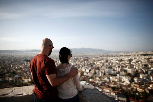 Visitors look at the view across the city from beneath the Parthenon temple on Acropolis Hill in Athens, Greece
