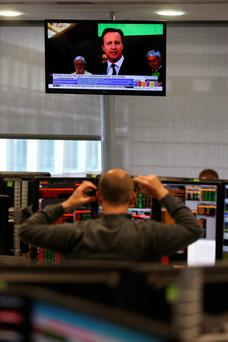 A television shows Prime Minister and Conservative Party leader David Cameron as traders work on the trading floor at Panmure Gordon & Co in London yesterday