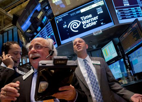 Traders work at the post where Time Warner Cable is traded on the floor of the New York Stock Exchange. Photo: Reuters