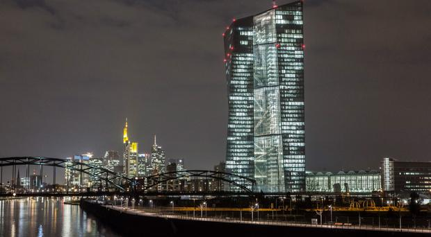 The European Central Bank (ECB) headquarters, right, are illuminated by light as the building stands on the skyline by the River Main in Frankfurt, Germany, on Friday, March 6, 2015. The final countdown is under way for the European Central Bank's program of government-bond purchases, which already fueled a debt-market rally that sent yields across the euro region to record lows. Photographer: Martin Leissl/Bloomberg