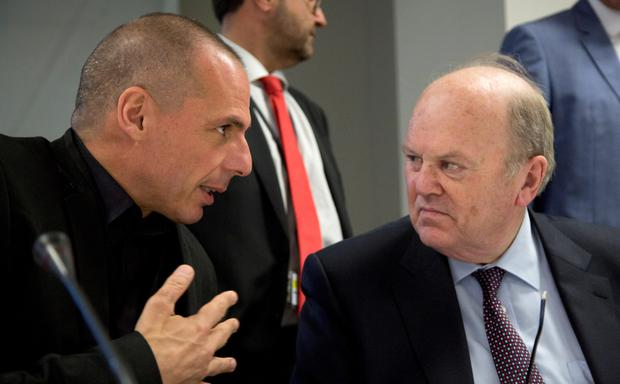 Greek Finance Minister Yanis Varoufakis, left, speaks with Irish Finance Minister Michael Noonan at the start of the annual meeting of the European Stability Mechanism Board in Luxembourg on Thursday, June 18, 2015. German Chancellor Angela Merkel is pressing Greece to deliver on commitments to carry out reforms, stressing that she wants the country to remain in the common currency. (AP Photo/Virginia Mayo)