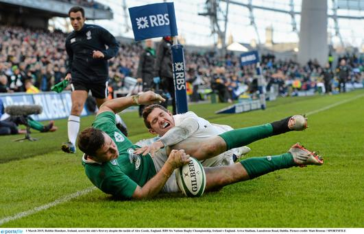 Robbie Henshaw, Ireland, scores his side's first try despite the tackle of Alex Goode, England at Dublin's Aviva Stadium last March