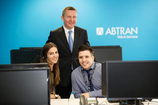 Michael Fitzgerald, chief executive of Abtran, with staff members Andrea Woods and Anthony Foley at the company's IFSC offices for yesterday's announcement. Photo: Conor McCabe
