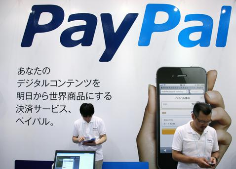 Staff members work in the Paypal Inc. booth at the 16th e-Book Expo Tokyo in Tokyo, Japan, on Thursday, July 5, 2012. The world largest trade show for e-book devices, contents and technologies is held through July 6. Photographer: Tomohiro Ohsumi/Bloomberg