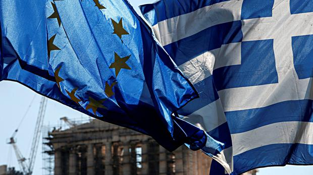 A European Union (EU) flag, left, flies beside a Greek national flag in front of the Parthenon temple on Acropolis Hill in Athens, Greece, on Wednesday, July 8, 2015. Photographer: Yorgos Karahalis/Bloomberg