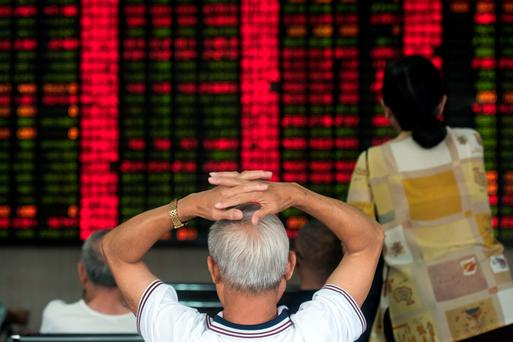 Investors monitor screens showing stock market movements at a brokerage house in Shanghai as shares slip again yesterday