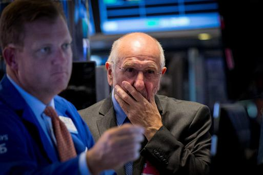Concern on the faces of New York Stock Exchange traders as Wall Street falls for the fourth consecutive day