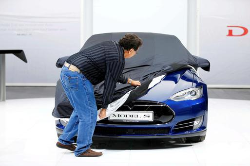 An employee covers a Tesla Model S car during the media day at the Frankfurt Motor Show.