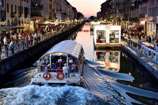 A boat sails along the The Naviglio Gran Canal in Milan