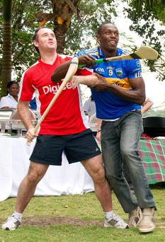 Digicel is a major player in dozens of countries, and it sponsors the likes of superstar athlete Usain Bolt, pictured top with Tipperary hurling great Eoin Kelly