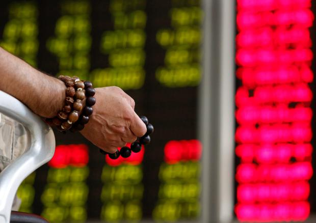 An investor holds onto prayer beads as he watches a board showing stock prices at a brokerage office in Beijing. Photo: Reuters