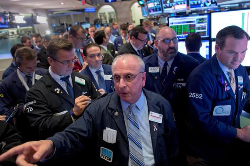 Traders gather at the post for Allergan stock on the floor of the New York Stock Exchange yesterday after Allergan and Pfizer confirmed they were in preliminary talks on a potential merger, a deal that would create the world's largest drugmaker. Photo: Reuters