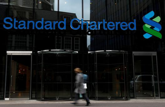 A woman walks past a Standard Chartered bank in London. Photo: Reuters