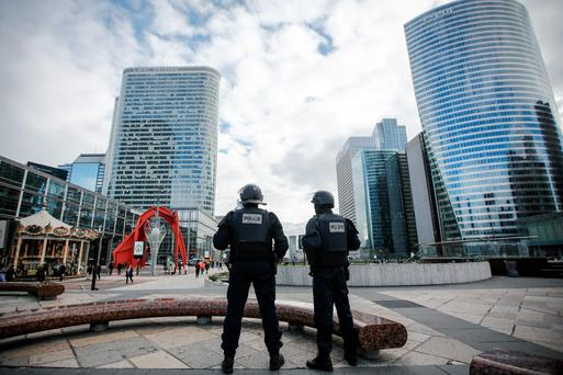 Armed police officers stand guard in the La Defense business district in Paris yesterday as Parisians returned to work following the terrorist attacks at the weekend