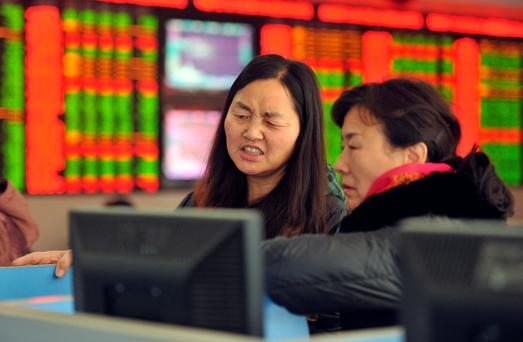 Two investors chat in a stock firm in Fuyang, east China's Anhui province. Photo: Getty Images