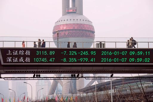 People walks along a pedestrian bridge with a screen showing stock market movements in Shanghai on January 7