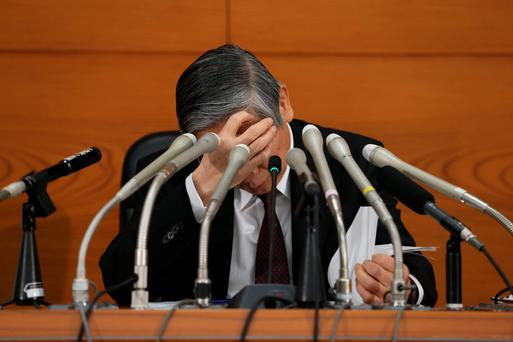 Haruhiko Kuroda, governor of the Bank of Japan, looks down at his notes during a news conference. Photo: Bloomberg