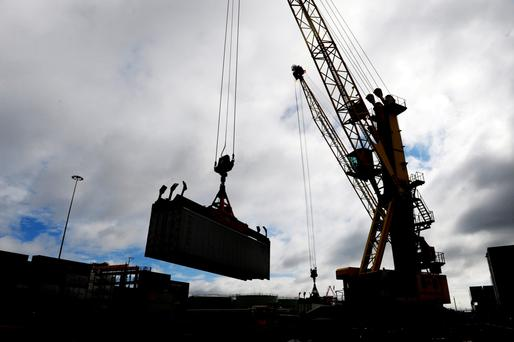 A crane transports a shipping container at Dublin port