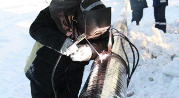 An engineer works on a Petroneft pipeline in Siberia