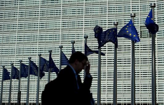 A pedestrian walks past the European Commission headquarters building in Brussels