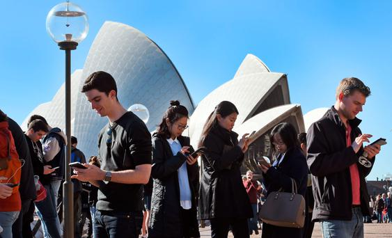 Dozens of people gather to play Pokémon Go in front of the Sydney Opera House as the app craze sweeps nations. Photo: Getty