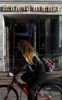 Cyclist passes by a Bank of Ireland branch in Belfast