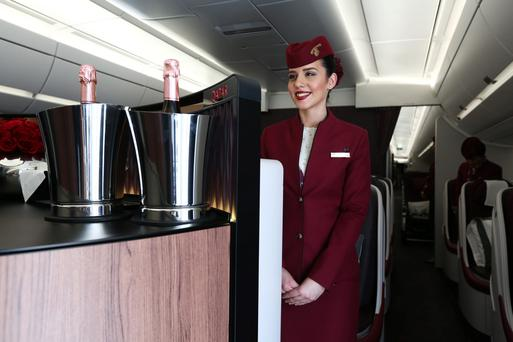A flight attendant at a bar in the business section of a Qatar Airways Airbus A350