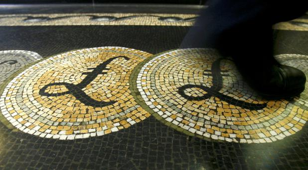 An employee walks over a pound symbol in the Bank of England, which is taking post-Brexit action