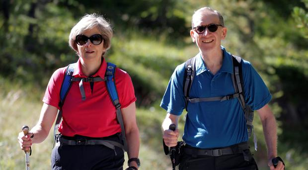 British Prime Minister Theresa May taking a hike in the Swiss Alps with her husband Philip John May while on summer holiday