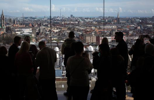 Visitors look out over the Dublin city skyline from the viewing gallery in the Guinness Gravity Bar based at the company's St. James's Gate Brewery, in Dublin