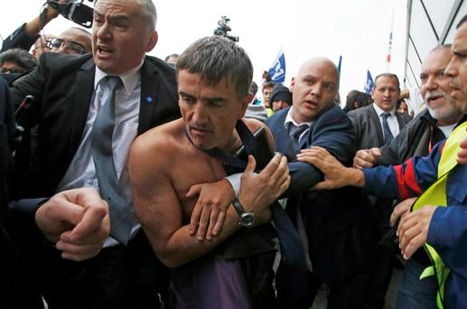 Xavier Broseta, executive vice president for human resources and labour relations at Air France, is evacuated by security after employees interrupted a meeting at the airline's HQ in October 2015