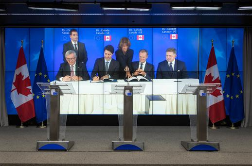 Jean-Claude Juncker, president of the European Commission; Justin Trudeau, Canada's prime minister; Donald Tusk, president of the European Union; and Robert Fico, Slovakia's prime minister, signing the Comprehensive Economic and Trade Agreement (CETA) in Brussels on October 30. Photo: Bloomberg