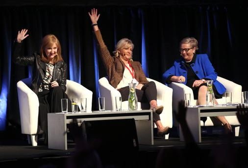 Lucy Gaffney, chairwoman, Communicorp, and Louise Phelan, vice president, PayPal, raise their hands in agreement that Tánaiste Francis Fitzgerald should become the next Taoiseach at the Planet Woman Academy in the RDS. Photo: Damien Eagers