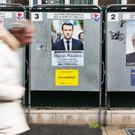 A man walks past electoral posters displaying candidates Benoit Hamon, Emmanuel Macron and Marine Le Pen in Paris. Photo: AP