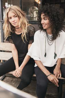 'Evie' black knit with lace sleeves, €74, and 'Bianca' knit tee, €64, and feather necklace, €126, on the Stella & Dot website