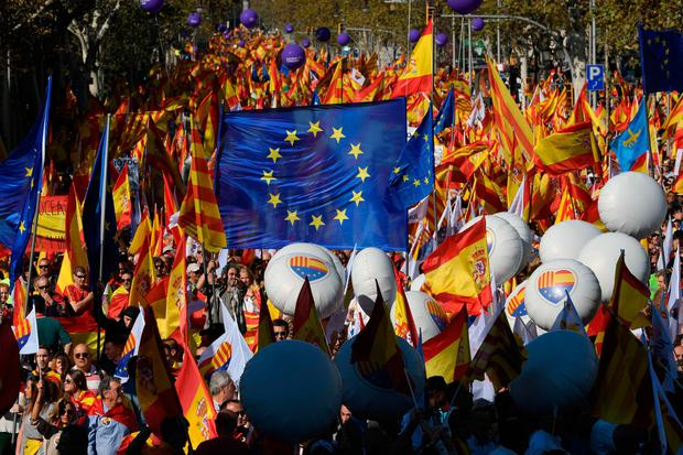 Protesters wave Spanish, Catalan and European Union flags during a pro-unity demonstration in Barcelona at the weekend