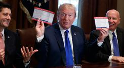 President Donald Trump holds an example of what a new tax form may look like during a meeting on tax policy with Republican politicians including House Speaker Paul Ryan
