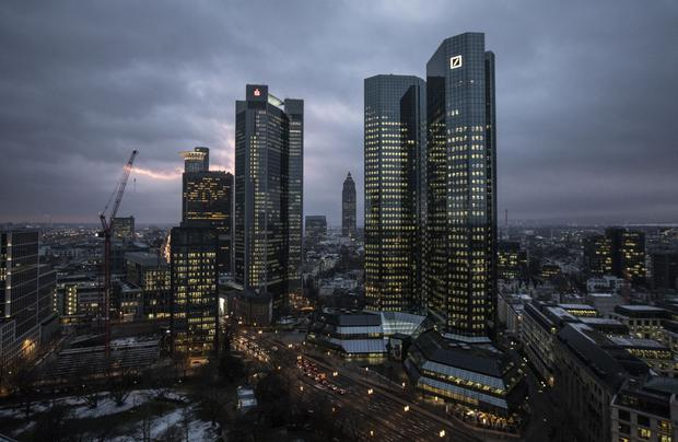 The twin tower skyscraper headquarter offices of Deutsche Bank, right, stand at dusk in Frankfurt