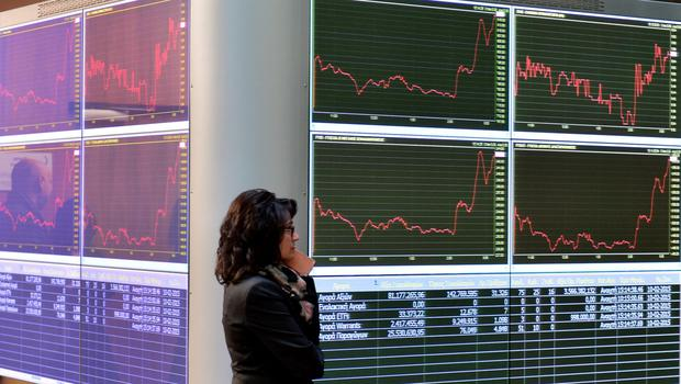 A worker at the Athens Stock Exchange stands in the reception hall as an electronic board displays stock prices. Getty Images